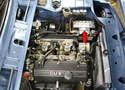 The battery for the BMW 2002 is located in the front left corner of the engine bay (red arrow).