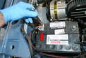 Next, remove the positive strap from the positive post on the battery with a 13mm wrench (red arrow) and set it aside.