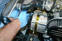 Gently push the alternator down and slide the belt off the alternator pulley.