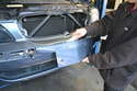 Using your trim removal tool gently pry out the license frame trim piece on the bumper cover.