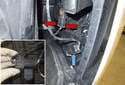 Working at the corner of the bumper, press the release tabs (red arrows) and unplug the fog light electrical connector.