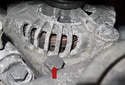 Working at the bottom front of the alternator, locate the 16mm alternator mounting fastener (red arrow).