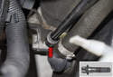 This photo shows the fastener being removed (red arrow).