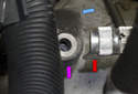 Then, remove the steering shaft coupler from the steering wheel shaft at the top by sliding it down and off (blue arrow).
