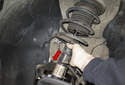 Carefully remove the strut assembly from the vehicle, bottom first (red arrow) then feed top out of fender.