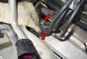 Working at the rear corner of the cylinder head, pull the wiring harnesses (red arrows) out of the holders.
