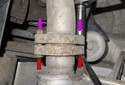 Working at the muffler to center pipe connection, counterhold the 13mm bolt (red arrow) while removing the 13mm nuts (purple arrows).