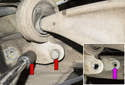 Working at rear of front control arm, remove two 16mm control arm bushing fasteners (red arrows).