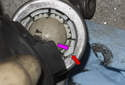 This photo shows the bushing tab (red arrow) moved into position with the slot (purple arrow) for removal.