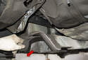 Remove the exhaust heat shield toward the rear of the vehicle (red arrow).