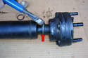 With pliers or diagonal cutters remove the band clamp (red arrow) that secures the CV joint boot to the shaft.
