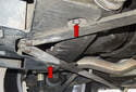 Working under the vehicle, behind the differential, remove the two 8mm fasteners (red arrows) for the plastic shield.