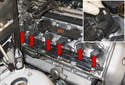 Unlock the ignition coil electrical connectors (red arrows) by pulling the tab up 90° and slide the electrical connector out of the ignition coil (inset).