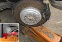 Place a hydraulic jack under trailing arm.