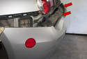 Once the corners are detached, continue to peel the bumper off the body, unclipping it at the center (red arrows).