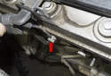 Working at the side of the cylinder head, remove the 13mm engine harness ground fastener (red arrow).