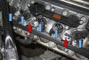 Unlock the ignition coil electrical connectors (blue arrows) by pulling the tab up 90 degrees and slide the electrical connector out of the ignition coil.
