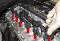 Remove the ignition coil from the cylinder head by pulling it straight up (red arrows).