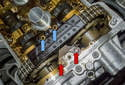 Working at the top of the cylinder head, remove the two 6mm Allen (blue arrows) and the two 10mm fasteners (red arrows).