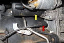 The crankshaft position sensor (red arrow) is located near (below) the starter motor (yellow arrow), mounted in the engine block (crankcase).
