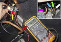 Connect DVOM across fuel pump terminals while backprobing (yellow arrows) then plug the connector (purple arrow) back in.