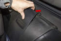 Unclip the top of the storage compartment trim (red arrow).