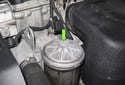 Using a 13mm socket on a six-inch extension, loosen the oil filter housing lid bolt (green arrow).