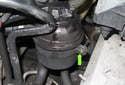 Start by loosening the 10mm reservoir bracket-clamping bolt (green arrow).