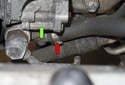 If you need to replace the hose that runs to the power steering pump (green arrow), remove the hose clamp for the low-pressure power steering hose (red arrow).