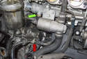 The sensor is located on a coolant pipe at the left front side of the cylinder head (green arrow).