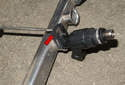 To remove individual fuel injectors, remove the retaining clip (red arrow) by sliding it off the fuel rail using a flathead screwdriver.
