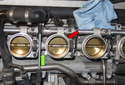 Each throttle body is held on by two fasteners - one at the top (red arrow) and one at the bottom (green arrow).