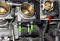 Intake camshaft sensor: Working under the cylinder six throttle body, remove the three 10mm wiring harness bracket nuts (green arrows).