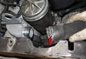 To remove the upper hose: using a flathead screwdriver, loosen the upper radiator hose clamp (red arrow).