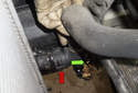 Working at the right side of the radiator, disconnect the lower radiator hose (green arrow).