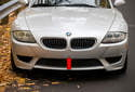 BMW Z4 models use a plastic bumper cover (red arrow) over a rigid strut-supported steel bumper.