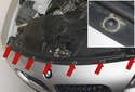 Working along the top of the radiator support, remove the seven T30 Torx bumper cover fasteners (red arrows).