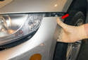 With all the fasteners removed from the front bumper, pull the front corners away (red arrow) from the headlights to detach it.