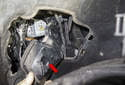 With the rod unclipped, remove the headlight bulb access cover (red arrow).