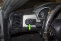 The headlight switch is located on the dashboard (green arrow).