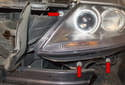 Working at the bottom and top of the headlight, remove the T25 Torx fasteners (red arrows).