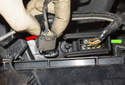 Slide the main electrical connector lock in the direction of the green arrow to unlock it.