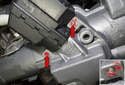 Working at the bottom of the steering column at the ignition switch, scrape out the ignition switch fastener paint (red arrows).
