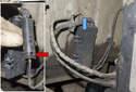 Working behind front strut, open plastic door (blue arrow) for brake pad wear sensor electrical connector.