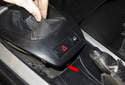 Using a plastic prying tool, lever the shift boot trim (red arrow) out of the center console.