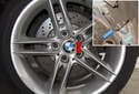 Remove one wheel stud per rear wheel while the vehicle is on the ground.