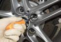 Using a long, thin flathead screwdriver, rotate the adjuster to down to back the parking brake shoes off.