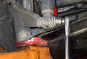 Remove rear shock 18mm mounting fastener (red arrow).