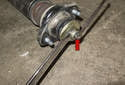 Using a 6mm wrench (or a pair of vise grips) and a 16mm or 17mm wrench, remove shock mount from shock (red arrows).