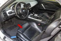 You may have to remove the seats (red arrow) from your BMW Z4 to replace them or service components beneath them, for example the seat belt buckle or front seat switches (blue arrows).